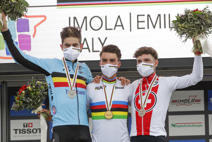 France's Julian Alaphilippe, center, winner of the men's elite event, poses on the podium with second placed Belgium's Wout van Aert, left, and third placed Switzerland's Marc Hirschi, at the road cycling World Championships, in Imola, Italy, Sunday, Sept. 27, 2020. (AP Photo/Andrew Medichini)