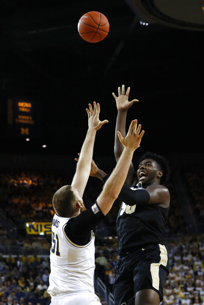 Purdue forward Trevion Williams (50) shoots over Michigan forward Austin Davis (51) in the first half of an NCAA college basketball game in Ann Arbor, Mich., Thursday, Jan. 9, 2020. (AP Photo/Paul Sancya)