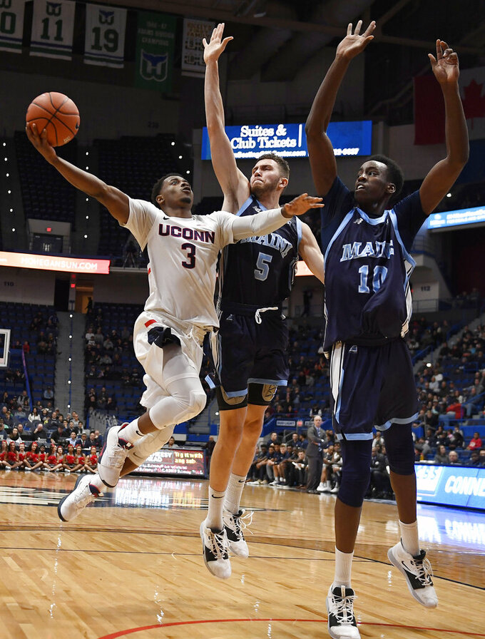 Connecticut's Alterique Gilbert shoots as Maine's Nedeljko Prijovic, center, and Maine's Stephane Ingo defend, right, during the first half of an NCAA college basketball game, Sunday, Dec. 1, 2019, in Hartford, Conn. (AP Photo/Jessica Hill)