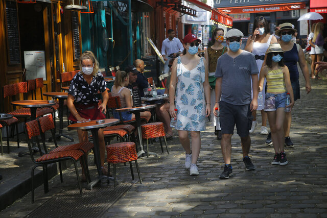 Tourists stroll the Montmartre district Monday, Aug. 10, 2020 in Paris. People are required to wear a mask outdoors starting on Monday in the most frequented areas of the French capital. The move comes as the country sees an uptick in virus infections. (AP Photo/Michel Euler)