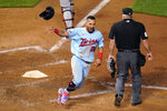 Minnesota Twins' Eddie Rosario tosses his helmet as he scores the winning run on a Max Kepler hit off Detroit Tigers' Bryan Garcia during the 10th inning of a baseball game Tuesday, Sept. 22, 2020, in Minneapolis. The Twins won 5-4. (AP Photo/Jim Mone)