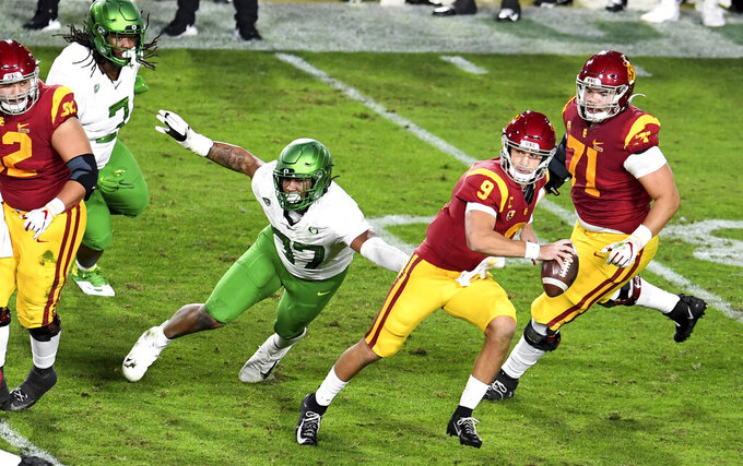 USC Quarterback Kedon Slovis scrambles against Oregon in the first half of an NCAA college football game at the Los Angeles Memorial Coliseum in Los Angeles on Friday, Dec. 18, 2020. (Keith Birmingham/The Orange County Register via AP)