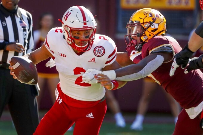 Minnesota defensive lineman Esezi Otomewo (9) drags Nebraska quarterback Adrian Martinez (2) into the end zone where he intentionally grounded the ball resulting in a safety in the fourth quarter of an NCAA college football game Saturday, Oct. 16, 2021, in Minneapolis. Minnesota won 30-23. (AP Photo/Bruce Kluckhohn)