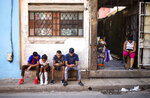 People surf the internet on their smartphones on the sidewalk in Havana, Cuba, Thursday, Dec. 6, 2018. For the first time, Cubans are able to sign up for 3G internet service for their mobile phones, with packages ranging from 600 megabytes for about $7 to four gigabytes for about $30 month. (AP Photo/Desmond Boylan)