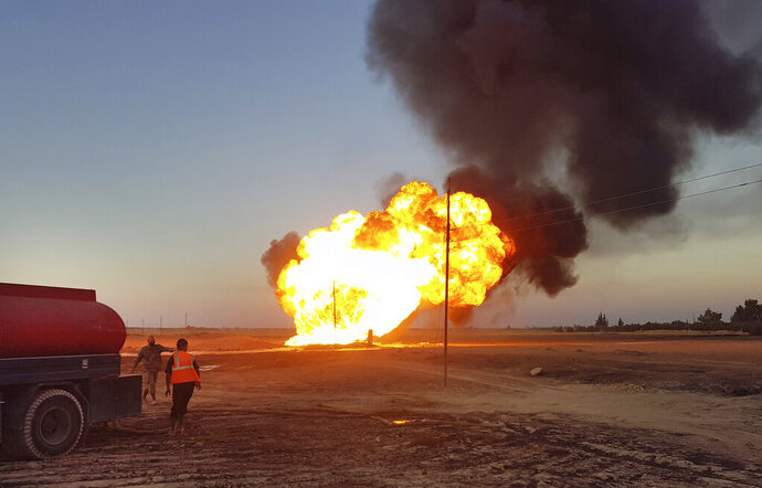 In this photo released by the Syrian official news agency SANA, flames rise from a gas pipeline that hit by an explosion, between the northeastern Damascus suburbs of Adra and Dumair, in Syria Monday, Aug. 24, 2020. An explosion early on Monday struck a gas pipeline in a Damascus suburb, cutting electricity throughout Syria, state media reported, citing the country's electricity and oil ministers. (SANA via AP)