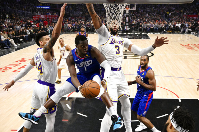 Los Angeles Clippers guard Reggie Jackson, second from left, tries to pass while under pressure from Los Angeles Lakers guard Danny Green, left, and forward Anthony Davis during the second half of an NBA basketball game Sunday, March 8, 2020, in Los Angeles. The Lakers won 112-103. (AP Photo/Mark J. Terrill)