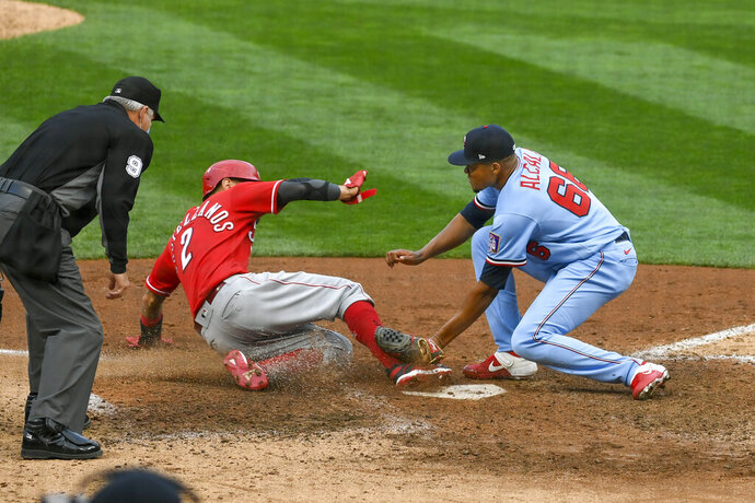 Minnesota Twins pitcher Jorge Alcala, right,tags out Cincinnati Reds' Nick Castellanosas he tries to steal home on a wild pitch during the tenth inning of a baseball game Sunday, Sept. 27, 2020, in Minneapolis. The Reds won 5-3. (AP Photo/Craig Lassig)