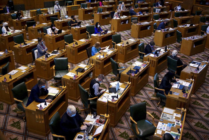 In this Wednesday, June 23, 2021, photo, lawmakers meet in the Oregon House of Representatives during the legislative session at the Oregon State Capitol in Salem, Ore. (Abigail Dollins/Statesman-Journal via AP)