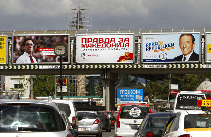 Campaign posters are set on an overpass in Skopje, North Macedonia, Friday, April 19, 2019. North Macedonia holds the first round of presidential elections on Sunday, a vote seen as key test for the center-left government's survival in a society deeply divided after the country changed its name to end a decades-old dispute with neighboring Greece over use of the term