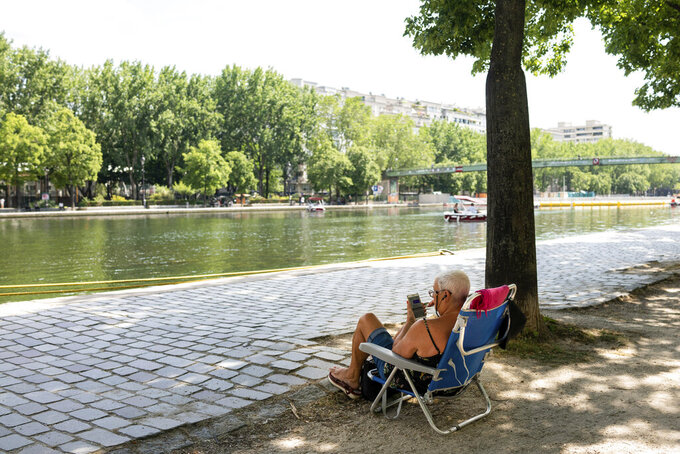 A man rests in the shadow along the Canal de l'Ourcq Wednesday, June 16, 2021 in Paris. Temperatures rose up to 33 degrees Celsius (91 degrees Fahrenheit) in the French capital. (AP Photo/Benjamin Girette)