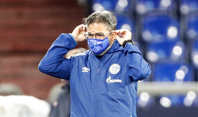 Schalke's head coach David Wagner preps his face mask prior the German Bundesliga soccer match between FC Schalke 04 and Werder Bremen in Gelsenkirchen, Germany, Saturday, Sept. 26, 2020. (AP Photo/Martin Meissner)