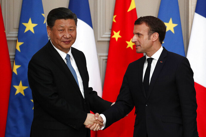 French President Emmanuel Macron, right, shakes hand with his Chinese counterpart Xi Jinping after a meeting at the Elysee Palace in Paris, France, Monday, March 25, 2019. Chinese President Xi Jinping was greeted with full honors Monday during a state visit to France in which he is expected to sign multibillion-dollar deals on energy, the food industry, transport and other sectors as well as a bilateral statement on climate change. (Yoan Valat/Pool Photo via AP)