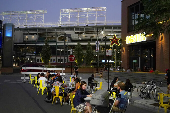 Patrons at the Big Star Wrigleyville restaurant Friday, Sept. 4, 2020, are seated in a social distant manner on West Patterson Ave., across from Wrigley Field during a baseball game between the Cubs and St Louis Cardinals in Chicago. The pandemic has been especially hard on businesses that rely on ballpark traffic, eliminating crowds at major league games, and leading to rules that limit the amount of people they can have inside their doors at the same time. (AP Photo/Charles Rex Arbogast)