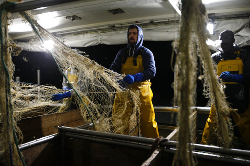 """FILE - In this Thursday, Dec. 10, 2020 file photo, fisherman Nicolas Bishop works on the Boulogne sur Mer based trawler """"Jeremy Florent II"""" in Boulogne-sur-Mer, northern France. The European Council adopted Tuesday, Sept. 28, 2021 a euro 5 billion (US dollar 5.8 billion) reserve aimed at helping businesses tackle the short-term negative effects of Brexit. Britain's departure has affected many parts of the EU economy, with the fishing sector particularly at risk. According to the European Commission, EU fisheries face a 25 percent reduction of their catch value in UK waters. (AP Photo/Michel Spingler, File)"""