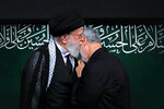 In this Sept. 30, 2017 photo, re-released Friday, Jan. 3, 2020, by an official website of the office of the Iranian supreme leader, Supreme Leader Ayatollah Ali Khamenei kisses Iranian Gen. Qassem Soleimani during a religious ceremony in Tehran, Iran. The re-release of the photo occured hours after Soleimani and others were killed in a U.S. drone strike, Friday, in Baghdad, Iraq. Their relationship was so close that Khamenei was photographed more than once embracing Soleimani in ways that are customary in Iran for fathers and their beloved sons. (Office of the Iranian Supreme Leader via AP)