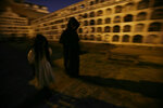 Guides walk under the moonlight at El Tejar cemetery, in downtown Quito, Ecuador, Wednesday, Sept. 11, 2019. The guides in black hooded capes lead tourists in the cemetery, navigating a maze of crypts as voices call out existential questions into the night. (AP Photo/Dolores Ochoa)