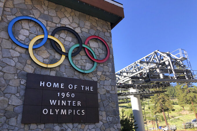 FILE - In this July 9, 2020, file photo, a sign marking the 1960 Winter Olympics is seen by a chairlift at Squaw Valley Ski Resort in Olympic Valley, Calif. Environmental lawyers are urging a California appellate court to overturn a pair of district court rulings that handed significant victories to the Squaw Valley ski resort as it moves forward with expansion plans critics say will dramatically increase traffic in the area and harm Lake Tahoe's air and water quality. (AP Photo/Haven Daley, File)