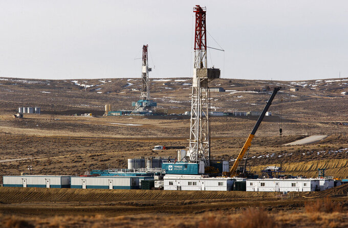 FILE - In this March 5, 2013, file photo, Trinidad Drilling rigs stand near Highway 59 outside Douglas, Wyo. In the closing months of the Trump administration, energy companies stockpiled enough drilling permits for western public lands to keep pumping oil for years. That stands to undercut President-elect Joe Biden's plans to block new drilling on public lands to address climate change. (Leah Millis/The Casper Star-Tribune via AP, File)