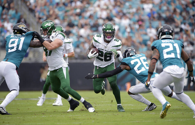"FILE - In this Oct. 27, 2019, file photo, New York Jets running back Le'Veon Bell (26) rushes for yardage in front of Jacksonville Jaguars defensive back Jarrod Wilson (26), defensive end Yannick Ngakoue (91) and cornerback A.J. Bouye (21) during the first half of an NFL football game in Jacksonville, Fla. Bell didn't like how little he was used in the 29-15 loss at Jacksonville, and Bell needed to make sure Jets coach Adam Gase knew what he was feeling. ""I was a little frustrated,"" Bell said Thursday. ""I'm always frustrated at a loss, but this was a little different because I wasn't involved and we lost."" Bell carried the ball eight times for 23 yards and had three catches for 12 yards. (AP Photo/Phelan M. Ebenhack, File)"