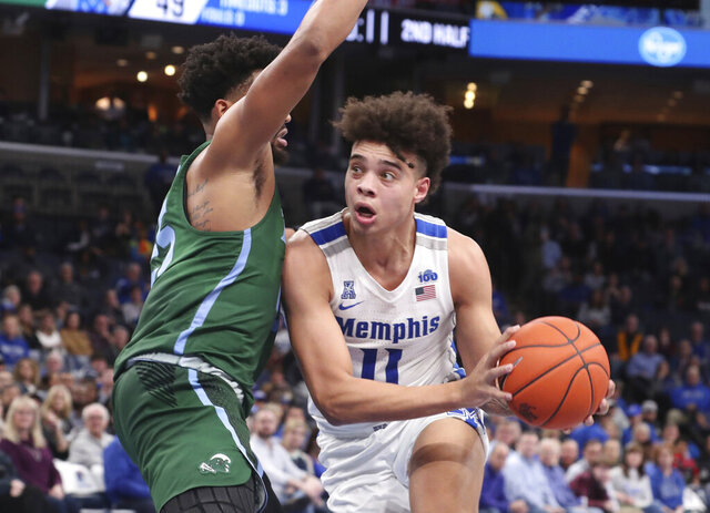 Memphis guard Lester Quinones (11) moves around Tulane guard Christion Thompson (25) in the second half of an NCAA college basketball game Monday, Dec. 30, 2019, in Memphis, Tenn. (AP Photo/Karen Pulfer Focht)