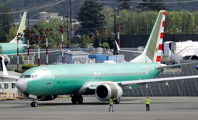 FILE - In this May 8, 2019, file photo, workers stand near a Boeing 737 Max 8 jetliner being built for American Airlines prior to a test flight in Renton, Wash. American Airlines is warning Boeing that it could cancel some overdue orders for the grounded 737 Max unless the plane maker helps line up new financing for the jets, which has become more expensive as the coronavirus pandemic has crippled airlines, according to people familiar with the discussions. (AP Photo/Ted S. Warren, File)