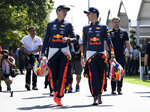 Red Bull driver Max Verstappen of the Netherlands, left, and teammate Pierre Gasly of France walk through the paddock ahead of the Australian Grand Prix in Melbourne, Australia, Thursday, March 14, 2019. (AP Photo/Andy Brownbill)
