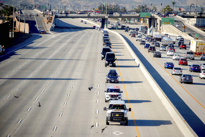 A hearse carrying the body of San Bernardino County Sheriff's Sgt. Dominic Vaca, along with a procession, travel north on the 215 Freeway through San Bernardino, on its way to his memorial service at the Glen Helen Amphitheate in San Bernardino, Calif., Friday, June 11, 2021. Sgt. A Southern California sheriff's sergeant who was shot and killed last week after an attempted traffic stop was memorialized Friday as a consummate professional and inspiring leader. (Watchara Phomicinda/The Orange County Register via AP)