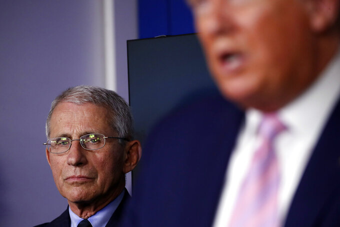 Dr. Anthony Fauci, director of the National Institute of Allergy and Infectious Diseases, listens as President Donald Trump speaks about the coronavirus in the James Brady Press Briefing Room of the White House, Wednesday, April 1, 2020, in Washington. (AP Photo/Alex Brandon)