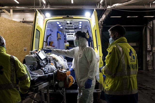 Ambulance crew work as a patient arrives at the CHR CItadelle hospital in Liege, Belgium, Thursday, Oct. 29, 2020. Belgium has announced restrictive measures across the country in an effort to curb the fast-rising tide of COVID-19, coronavirus cases. (AP Photo/Valentin Bianchi)