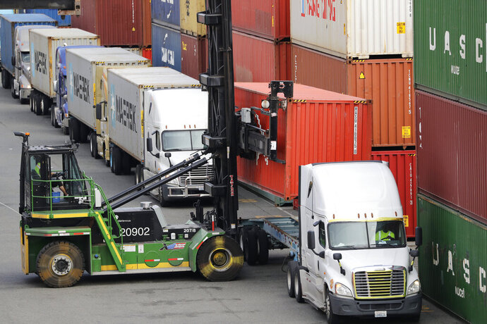 FILE - In this Oct. 2, 2019, file photo a shipping container is lifted off the back of a truck as others wait in line to have their cargo unloaded at a terminal on Harbor Island in Seattle. On Thursday, Dec. 5, the Commerce Department reports on the U.S. trade gap for October. (AP Photo/Elaine Thompson, File)