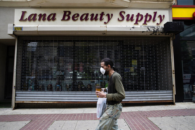 A shopper in a mask walks in front of a shuttered store in downtown Allentown, Pa., Friday, May 29, 2020. Unfilled potholes, uncollected trash, un-mowed grass and, most significantly, fewer cops on the street are some of what the city of Allentown, Pennsylvania, says it's facing unless Washington helps it plug a multimillion-dollar budget hole left by the pandemic. (AP Photo/Matt Rourke)
