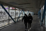 In this Monday, Feb. 10, 2020, photo, a couple wearing protective face masks walks past peeled off posters made by pro-democracy protesters at a footbridge in Hong Kong. The city's often-tumultuous street protests had already slowed in the past two months. Now they have ground to an almost complete halt as attention focuses on how to avoid a recurrence of the SARS pandemic, which killed about 300 people in Hong Kong in 2002-03.(AP Photo/Vincent Yu)
