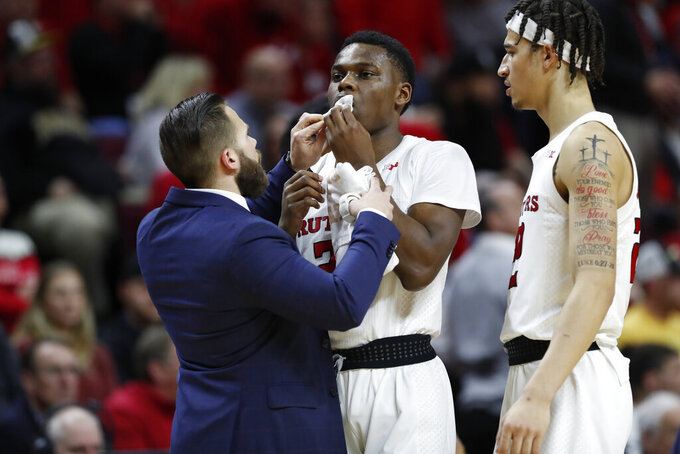 A team trainer attends to Rutgers guard Montez Mathis (23) after he was thrwon to the court by a Purdue defender during the first half of an NCAA college basketball game, Tuesday, Jan. 28, 2020, in Piscataway, N.J. The Purdue player was charged with a flagrant foul in the incident. (AP Photo/Kathy Willens)