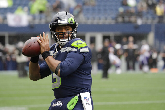 Seattle Seahawks quarterback Russell Wilson passes during warmups before an NFL football game against the Baltimore Ravens, Sunday, Oct. 20, 2019, in Seattle. (AP Photo/Elaine Thompson)
