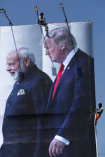 FILE - In this Feb. 20, 2020, file photo, workers install a giant hoarding welcoming U.S. President Donald Trump ahead of his visit, in Ahmedabad, India. To welcome Trump, who last year likened Modi to Elvis Presley for his crowd-pulling power at a rally in Houston, the Gujarat government has spent almost $14 million on ads blanketing the city that show the two leaders holding up their hands, flanked by the Indian and U.S. flags. It also scrambled to build a wall to hide a slum from the road Trump and first lady Melania Trump will travel, caught stray dogs, planted exotic trees and is rushing to finish a cricket stadium in time for Trump's arrival. (AP Photo/Ajit Solanki, File)