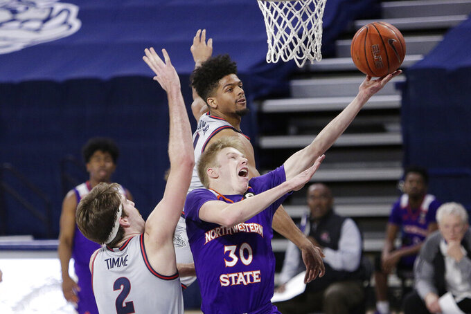 Northwestern State guard Trenton Massner, center, shoots between Gonzaga forward Drew Timme, left, and guard Aaron Cook during the second half of an NCAA college basketball game in Spokane, Wash., Tuesday, Dec. 22, 2020. Gonzaga won 95-78. (AP Photo/Young Kwak)