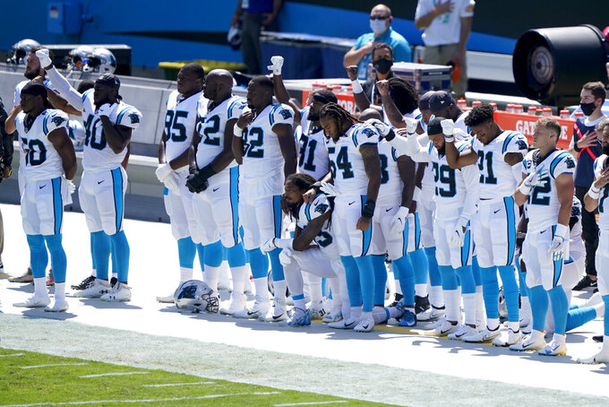 Members of the Carolina Panthers gesture during the Nation Anthem before an NFL football game against the Las Vegas Raiders Sunday, Sept. 13, 2020, in Charlotte, N.C. (AP Photo/Brian Blanco)