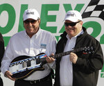 FILE - In this Jan. 30, 2011, file photo, car owners Felix Sabates, left, and Chip Ganassi hold a guitar trophy after winning the Grand Am Rolex 24 hour auto race at Daytona International Speedway in Daytona Beach, Fla. Felix Sabates is leaving NASCAR after 30 years as a team owner. His record shows 50 Cup wins, including victories at the crown jewels Daytona 500, Brickyard 400 and NASCAR's All-Star race. He also coaxed Ganassi into sports car racing and the IMSA teams won 64 races and seven series championships. (AP Photo/John Raoux, File)