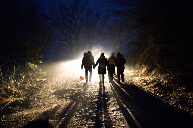 In this picture taken Thursday Dec. 12, 2019, Indian migrants Nishademi, 22, and Suhil, 23, walk with Saif, 33, Fatma, 24, and their son Omar, 1, Syrian refugees form Aleppo walk towards the border with Croatia as they attempt to enter the EU in the mountains surrounding the town of Bihac, northwestern Bosnia. (AP Photo/Manu Brabo)