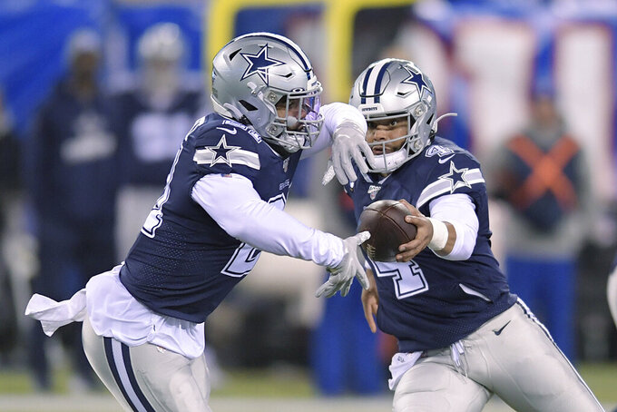 Dallas Cowboys quarterback Dak Prescott (4) hands off the ball to running back Ezekiel Elliott (21) during the first quarter of an NFL football game against the New York Giants, Monday, Nov. 4, 2019, in East Rutherford, N.J. (AP Photo/Bill Kostroun)