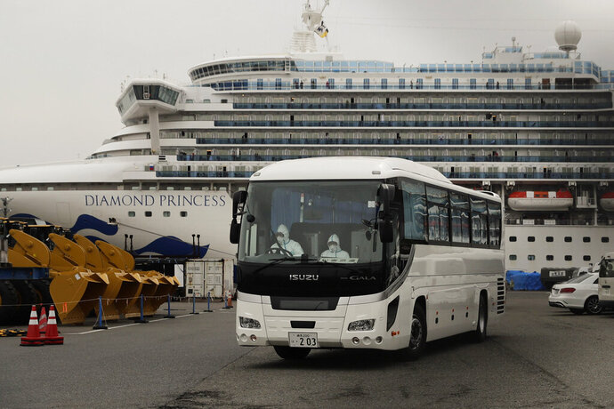 A bus leaves a port where the quarantined Diamond Princess cruise ship is docked Saturday, Feb. 15, 2020, in Yokohama, near Tokyo. A viral outbreak that began in China has infected more than 67,000 people globally. The World Health Organization has named the illness COVID-19, referring to its origin late last year and the coronavirus that causes it. (AP Photo/Jae C. Hong)