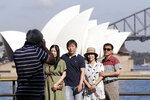 In this Jan. 22, 2020, photo, tourists gather to have their photos taken with the Opera House and Harbour Bridge as a backdrop in Sydney, Australia. Tourism Australia, a government agency tasked with promoting the country overseas, has taken steps to counter mainstream media messages that Australia is a nation on fire, pointing out that many tourist attractions have not been affected by the crisis. (AP Photo/Rick Rycroft)