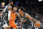 San Antonio Spurs' DeMar DeRozan (10) drives against Phoenix Suns' Kelly Oubre, Jr. (3) as he is screened by Spurs forward LaMarcus Aldridge during the first half of an NBA basketball game, Friday, Jan. 24, 2020, in San Antonio. (AP Photo/Darren Abate)