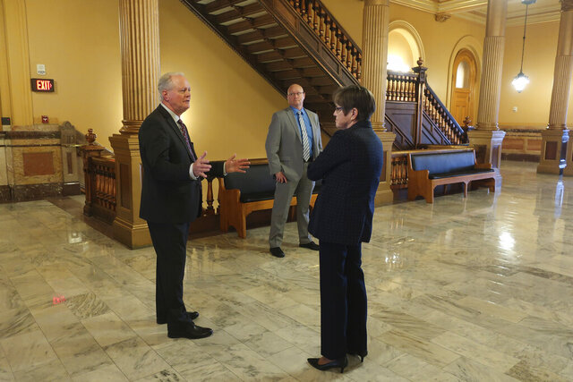 Kansas state Sen. Gene Suellentrop, left, R-Wichita, speaks with Democratic Gov. Laura Kelly, right, outside her Statehouse office, as her security officer watches, Thursday, March 19, 2020, in Topeka, Kan. Kelly is practicing social distancing during the coronavirus pandemic. (AP Photo/John Hanna)