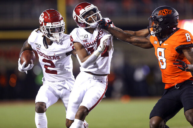 Oklahoma wide receiver CeeDee Lamb (2) runs after a catch while wide receiver Lee Morris (84) blocks Oklahoma State cornerback Rodarius Williams (8) during an NCAA college football game, Saturday, Nov. 30, 2019, in Stillwater, Okla. (Ian Maule/Tulsa World via AP)
