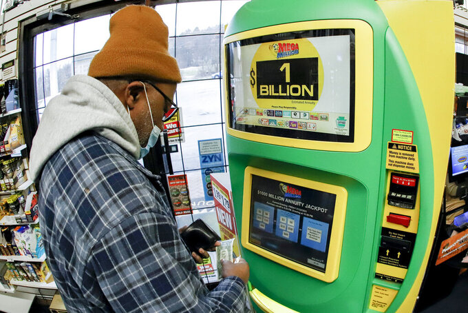 A patron, who did not want to give his name, uses the lottery ticket vending kiosk at a Smoker Friendly store to purchase tickets for the Mega Millions lottery drawing, Friday, Jan. 22, 2021, in Cranberry Township, Pa. The jackpot for the Mega Millions lottery game has grown to $1 billion ahead of Friday night's drawing after more than four months without a winner. (AP Photo/Keith Srakocic)