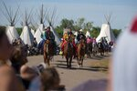 Participants ride in the morning parade at Crow Fair in Crow Agency, south of Billings, Mont., on Aug. 18, 2019.The Crow Tribe in Montana ordered its members to lock down for two weeks as tribal leaders moved to slow a sharp spike in coronavirus cases. (Mike Clark/The Billings Gazette via AP)