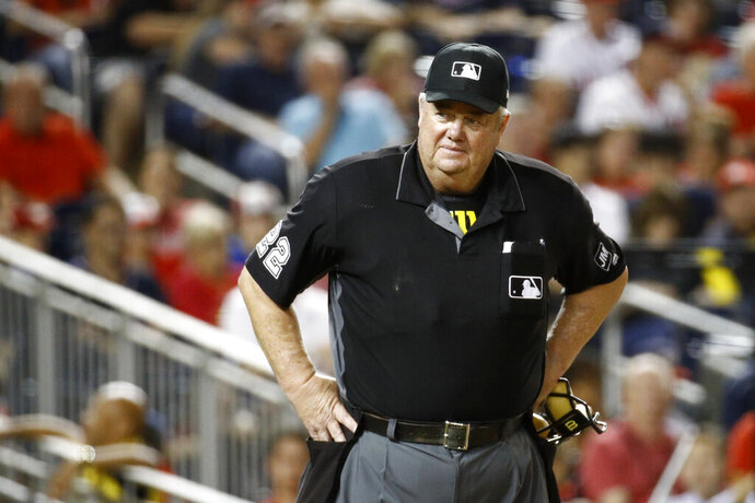 FILE- In this Sept. 27, 2019, file photo, umpire Joe West stands on the field during a baseball game between the Cleveland Indians and the Washington Nationals in Washington. West has sued retired player Paul LoDuca for defamation after the former catcher alleged West gave pitcher Bill Wagner a bigger strike zone in exchange for letting the umpire borrow a vintage car. (AP Photo/Patrick Semansky, File)
