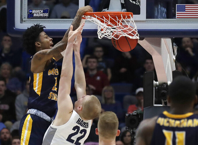 Murray State's Ja Morant, left, dunks over Marquette's Joey Hauser (22) during the second half of a first round men's college basketball game in the NCAA Tournament, Thursday, March 21, 2019, in Hartford, Conn. (AP Photo/Elise Amendola)