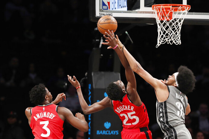 Brooklyn Nets center Jarrett Allen (31) gets his hand on the hand of Toronto Raptors forward Chris Boucher (25) as Raptors forward OG Anunoby (3) looks on during the first quarter of an NBA basketball game, Wednesday, Feb. 12, 2020, in New York. (AP Photo/Kathy Willens)